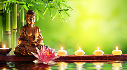 Panel Szklany Popularne Buddha Statue With Candles In Natural Background