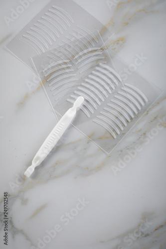 Fotografie, Obraz  Künstliche Augen Lidfalten Tape Klebeband gegen Schlupflid auf Marmor Hintergrun