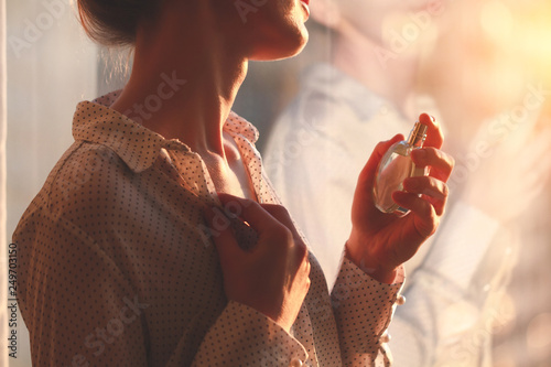 Fototapeta Stylish woman in blouse spraying a bottle of favorite perfume at sunset. Fashion, beauty and style obraz