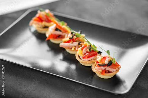 Photo  Delicious appetizer with ham, cheese, pepper and tomato in tartlets
