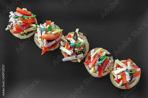 Delicious French snack with ham, cheese, pepper and tomato in tartlets Canvas Print