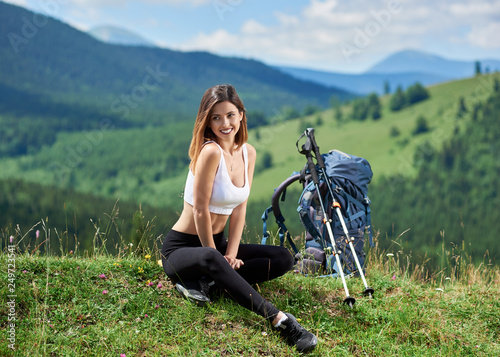 Obraz Sporty female tourist with backpack and trekking poles sitting on a grass, on the top of a hill, smiling and looking away, enjoying sunny day in the mountains. Copy space - fototapety do salonu