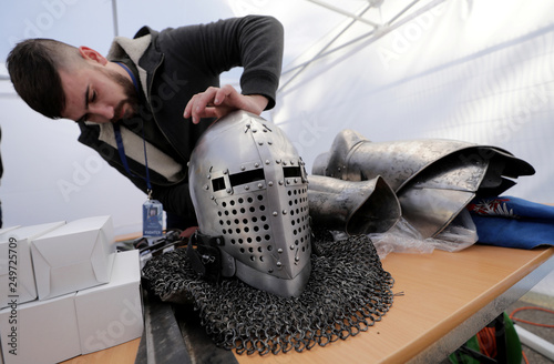 A competitor of Buhurt Prime checks his helmet before the