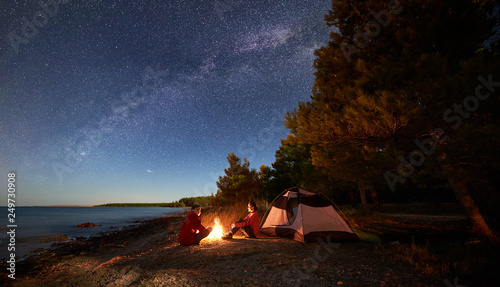 Fototapeta Night camping on shore. Young man and woman tourists sitting relaxed in front of tent at campfire under starry sky with Milky way on blue water and forest background. Active outdoor lifestyle concept obraz na płótnie