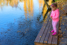 Adorable Happy Girl Feeding Fish In Autumn Park. Young Female Throwing Bread In To The Lake To Feed Fish. Pretty Little Girl In Pink Sport Dress Stands On Wooden Pier. Small Cute Child Feeding Fish.