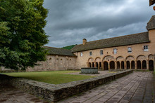 Fountain And Arcade In The Interior Courtyard Of The Conques Monastery