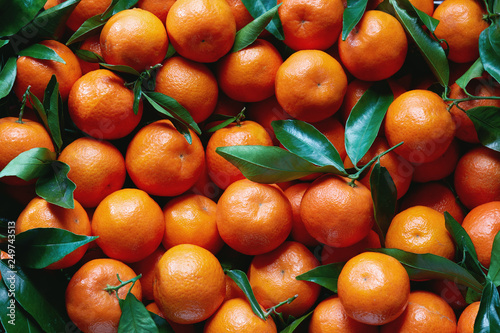 Canvastavla Fresh tangerines with stems and leaves, for sale at market.