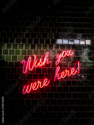 Fotografía 80's styled red neon text Wish you were here on a black tiles wall background