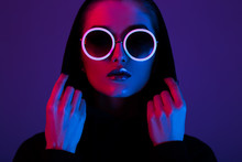 Portrait Of Fashion Young Girl In A Black Sweater With A Hood And Round Sunglasses In Red And Blue Neon Light In The Studio