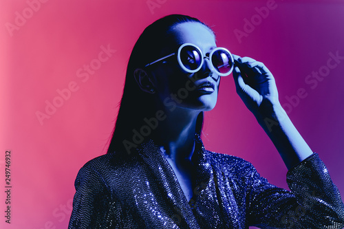 Fototapeta  Fashion girl with long hair and round sunglasses in a black shining dress poses