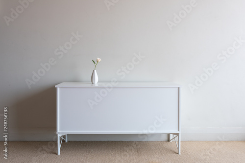 Valokuva  Single pale pink rose in smal vase on white sideboard against neutral wall backg
