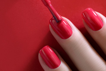 Red Finger nail point isolated red background with nail polish. Painting nails.