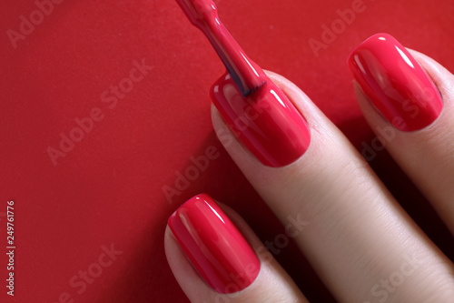 Fotografering Red Finger nail point isolated red background with nail polish