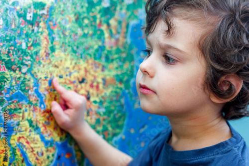 The curly-headed Child with interest looks at the blue world map Canvas-taulu