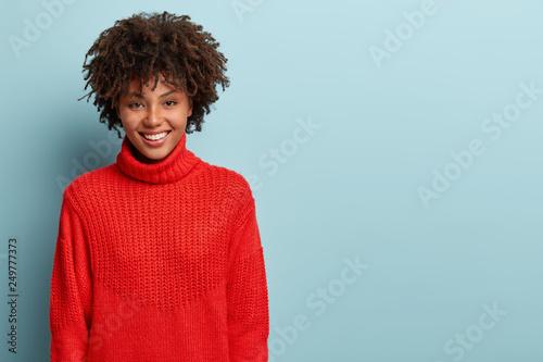 Fotomural Sincere feminine girl with dark skin, crisp hair, broad smile, has fun, enjoys e