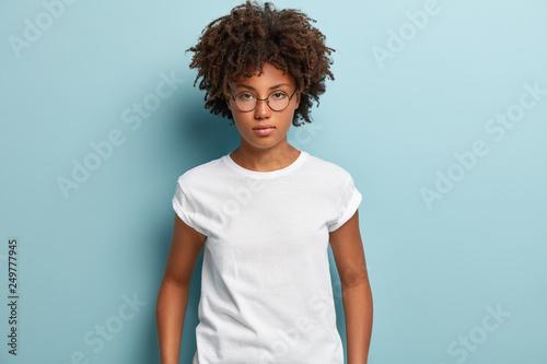 Fotografiet  Studio shot of serious thoughtful feminine girl with dark skin, crisp hair, look