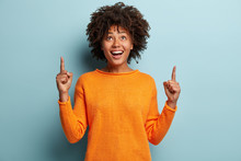 Horizontal Shot Of Positive Optimisitc African American Woman Points With Both Fore Fingers Upwards, Wears Casual Jumper, Advertises New Item, Isolated Over Blue Background. Look At This Thing