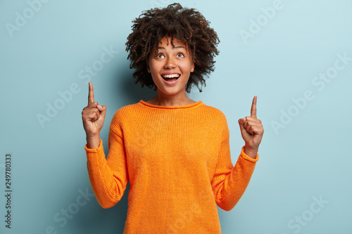 Fotografie, Tablou  Horizontal shot of positive optimisitc African American woman points with both fore fingers upwards, wears casual jumper, advertises new item, isolated over blue background