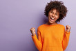 canvas print picture - Life is wonderful! Joyful dark skinned lady keeps fists clenched, tilts head and exclaims in triumph, celebrates success, isolated over purple background with blank space for your advertisement