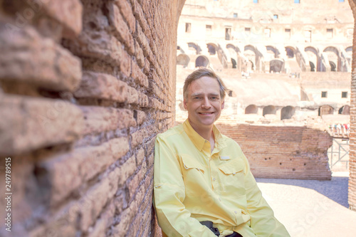 Photo  Caucasian man in late forties sitting inside Colloseum in Rome
