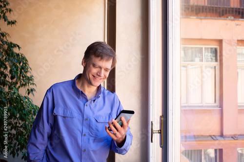 Fotografía  Caucasian man standing by large window looking at smartphone, smiling