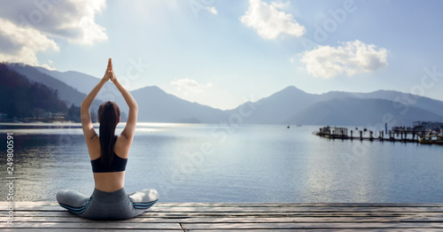 Obraz Young woman practicing yoga in the nature - fototapety do salonu