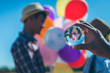 Reflection of couples with balloons in a glass ball in a handle