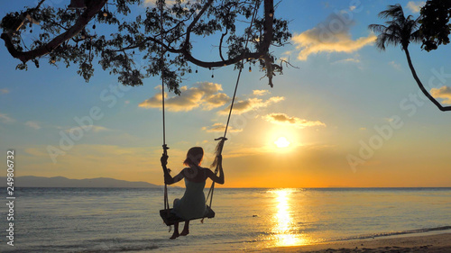 Back view Woman Silhouette on Swing, Sea view with brightly Sunset colors on background