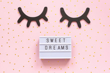 Lightbox Text Sweet Dreams And Decorative Wooden Black Eyelashes, Closed Eyes Gold Star On Pink Paper Background. Concept Good Night Greeting Card Top View Creative Flat Lay