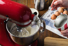 Pouring Sugar Into Bowl Of Red Standing Kitchen Aid Mixer On Wooden Table