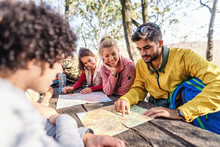 Hikers Sitting And Watching At Maps. Bearded Man Pointing At Map. Nature In Autumn Exterior.