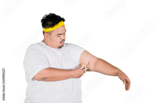 Photo Asian fat man measures fat layer of his arm on studio