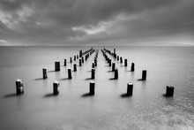 Wooden Poles On Baltic Sea Beach In High Contrast Evening Light With Clouds In Windy Weather, Water Movement In Long Exposure - Location: Baltic Sea, Rügen Island