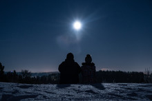 Silhouette Of A Man And Woman Sitting On A Snow Covered Hill At Night And Looking At The Moon