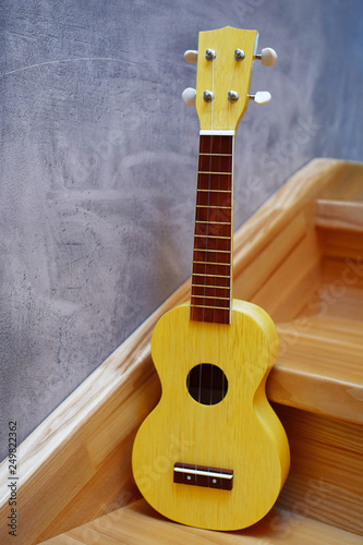 Fotografija  Yellow traditional soprano ukulele guitar on natural wooden stairs steps and grey grunge plaster wall background