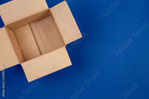 Fototapeta Open empty cardboard boxes on blue background
