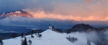 Panoramic View Of Beautiful Winter Wonderland Mountain Scenery In The Alps With Pilgrimage Church Of Jamnik And Famous Julian Alps In The Background, Bled, Slovenia. Christmas Time In Europe Concept