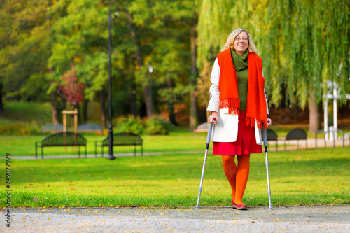 Photographie happy woman practicing walking on crutches