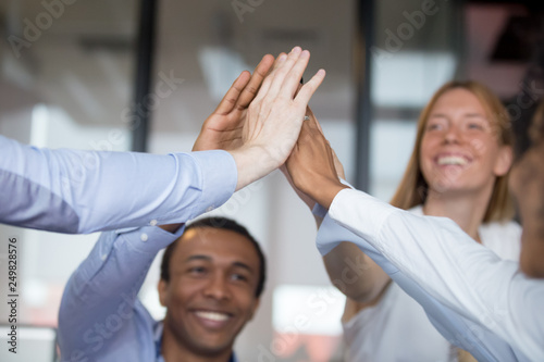 Happy diverse businesspeople giving high five closeup focus on hands Canvas Print