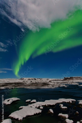 Foto auf Gartenposter Nordlicht Aurora borealis, Iceland. Green northern lights. Starry sky with polar lights. Night winter landscape with aurora, sea with sky reflection and snowy mountains and black beach. Nature background