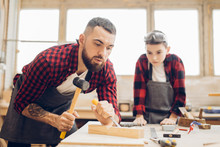 Bearded Jointer Man In Safety Glasses And An Apron Works With Chisel In A Carpentry Shop. Carpenter Holding A Chisel And His Son Watching The Process.