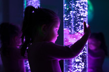 Child In Therapy Sensory Stimulating Room, Snoezelen. Child Interacting With Colored Lights Bubble Tube Lamp During Therapy Session.