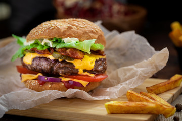 Fresh tasty burger and french fries on wooden table