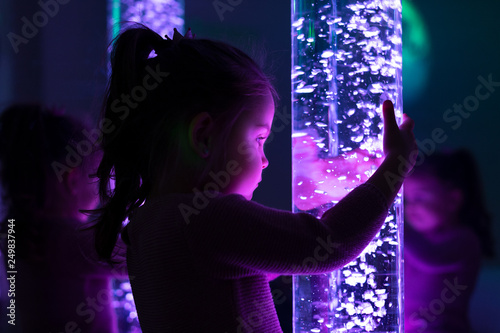 Fototapeta Child in therapy sensory stimulating room, snoezelen. Child interacting with colored lights bubble tube lamp during therapy session. obraz