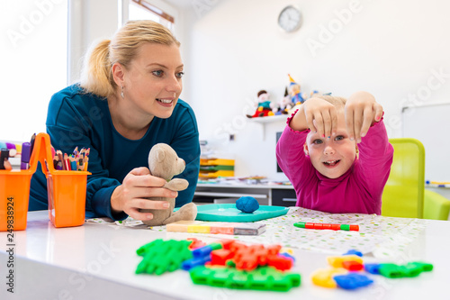 Fotografie, Obraz  Toddler girl in child occupational therapy session doing sensory playful exercises with her therapist