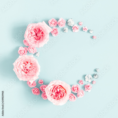 Flowers composition. Wreath made of rose flowers on pastel blue background. Mothers day, womens day, spring concept. Flat lay, top view, copy space, square