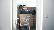 Man hold meme sign Will Film For Any Money. Static shot of a male person in front of a glass door knock and holding a sign with words.