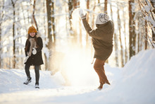 Full Length Portrait Of Happy Little Girl Throwing Snow At Father While Having Fun In Winter Forest Lit By Sunlight, Copy Space