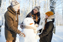 Portrait Of Happy Family Building Snowman In Winter Forest And Laughing, Copy Space