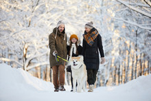 Full Length Portrait Of Happy Family Enjoying Walk With Dog In Winter Forest, Copy Space